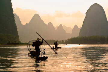 Silhouette of cormorant fishermen on the Li River (Lijiang) with karst peaks in the background at sunset, near Xingping, Guangxi Province, China