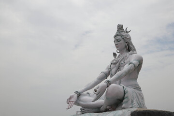 RISHIKESH, INDIA , Statue of Shiva, Hindu idol near Ganges River water, Rishikesh, India. The first Hindu God Shiva. Sacred places for pilgrims in Rishikesh