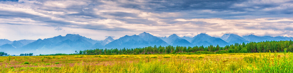 Panoramic summer landscape of mountain range with peaks, valley with green grass, grove and cloudy sky. Natural background with space for text. Eastern Sayan, Tunka National Park, Buryatia, Russia