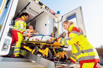 Paramedics putting injured man on stretcher in ambulance car