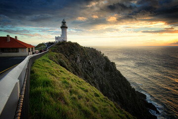 Lighthouse Amidst Sea And Buildings Against Sky During Sunset