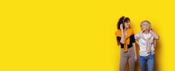 Curly haired students listening to music on a yellow wall with free space while looking at each other and smile