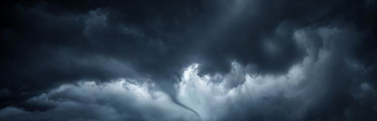 The typhoon is born, a tornado in a stormy dark sky with black clouds .Panoramic image. Concept on the theme of weather, natural disasters, tornadoes, typhoons, tornadoes, thunderstorm.