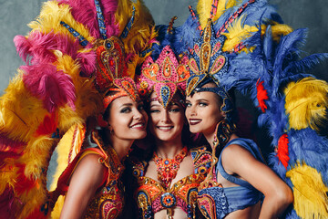 Three Women smiling portrait in brazilian samba carnival costume with colorful feathers plumage.
