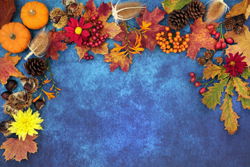 Autumn harvest festival background border with food, flora and fauna on mottled blue grunge background. Top view.
