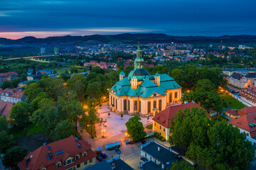 Aerial view of baroque church temple in the heart of Karkonosze mountains in Jelenia Gora surrounded by old city architecture at beautiful sunset. Photo taken from drone. Popular tourist destination