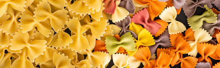 top view of raw colorful fusilli and farfalle pasta