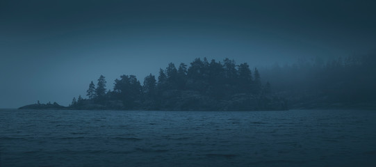 Silhouette of a forested island lost in the fog