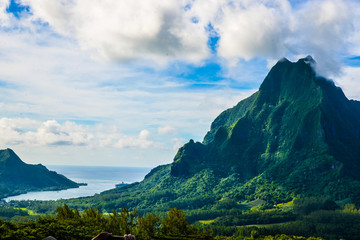 Moorea, French Polynesia: 09/03/2018: Total lanscape of the colorful main mountain in Moorea, everywhere is green and a blue sky