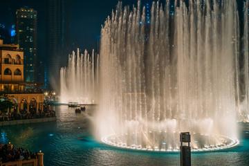 Dancing fountain show in Dubai center in evening, UAE. Tourist attraction.