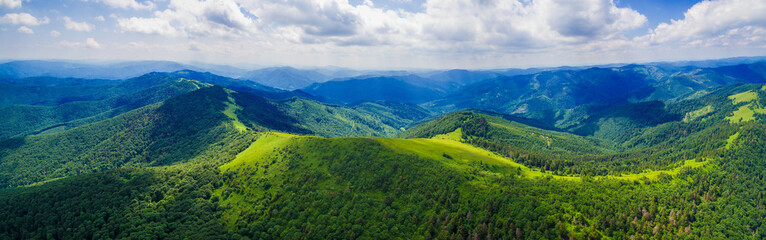 Aerial drone panorama of the Carpathian Mountains, with flowering summer meadows, blue mountains and white clouds in the sky.