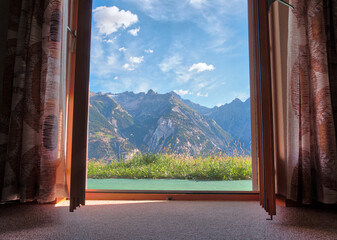 Mountain landscape view trough window with curtains in cozy home, beautiful summer view in Switzerland