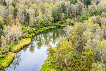 Top view of the river in the Siberian taiga among the forests in autumn