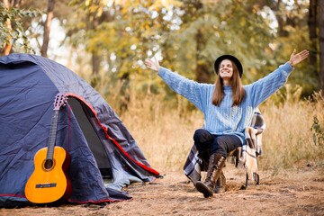 Young woman in warm sweater and black hat resting with guitar near camping tent in wilderness forest