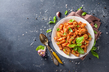 Fusilli pasta with tomato sauce and basil. Traditional italian Fusilli pasta marinara, on dark background copy space