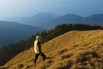 A man watch toward the mountain with golden grassland.