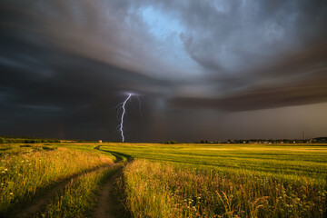 rural road in the middle of a field and a flash of lightning in the dramatic sky