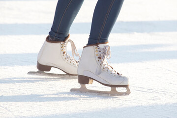 legs of a woman in blue jeans and white skates on an ice rink. hobbies and leisure. winter sports