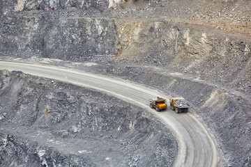 Top view of working BelAZ dump trucks in a stone and crushed stone quarry in Russia, Chelyabinsk region, Miass city