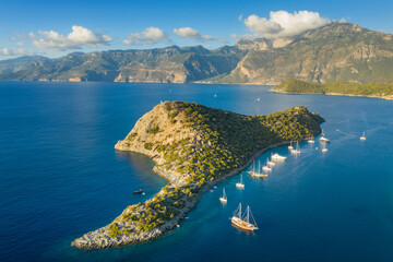 aerial view to island in sun light with yachts under blue sky and clouds on the tops