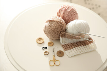 Yarn balls and knitting accessories on white table. Creative hobby