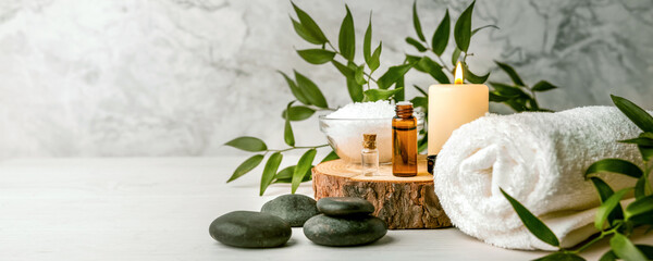 beauty treatment items for spa procedures on white wooden table. massage stones, essential oils and sea salt. copy space