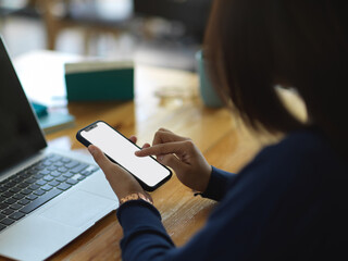Female hands using smartphone while working with laptop in office room