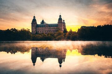 The Schloss or Burg Johannisburg in Aschaffenburg in spring, spring. Reflection in the river Main, sunrise mist and unbelievable atmosphere