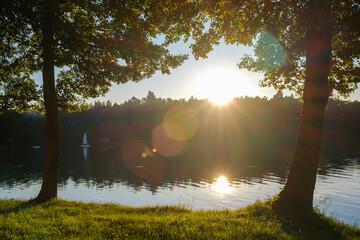 Słońce zachodzi z flarą i promieniami między drzewami nad jeziorem latem w ciepły wakacyjny dzień z kempingiem w tle