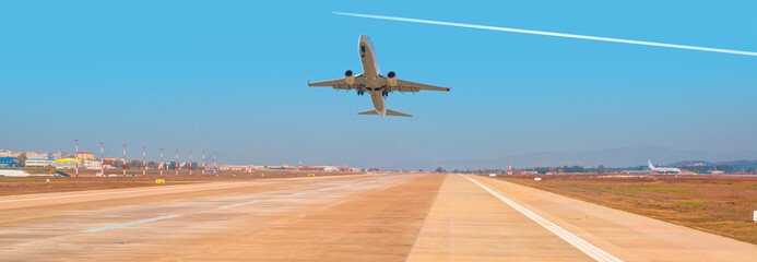 White Passenger plane fly up over take-off runway from airport