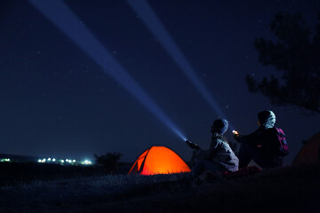 Couple with flashlights near camping tent outdoors at night