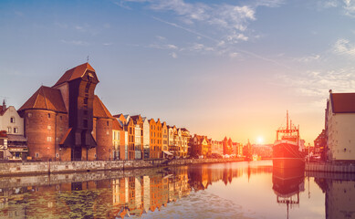 Waterfront of Gdansk with reflection on a sunrise, at dawn. Clear day, blue sky, feather clouds, rising Sun with flare, toned image. Historic part of Gdansk, tourist attraction in Poland.
