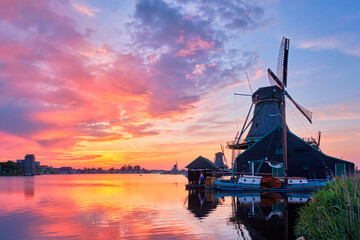 Netherlands rural scene - - windmills at famous tourist site Zaanse Schans in Holland on sunset with dramatic sky. Zaandam, Netherlands