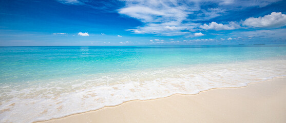 Closeup of sand on beach and blue summer sky. Panoramic beach landscape. Empty tropical beach and seascape. Blue sky, soft sand, calmness, tranquil relaxing sunlight, summer mood. Travel vacation
