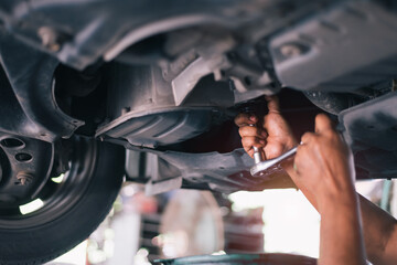 Mid adult mechanic repairing undercarriage of a car in auto repair shop.