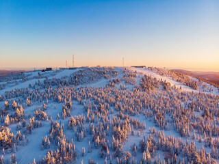 Colorful winter sunset in Sheregesh ski resort mountains covered trees. Aerial top view beautiful forest of Russia