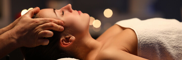 Woman lay on couch on her back with closed eyes and enjoy. Man make relaxing and therapeutic head massage at weight. Spa client has thrown her head back and rejuvenate. Wellness procedures in spa