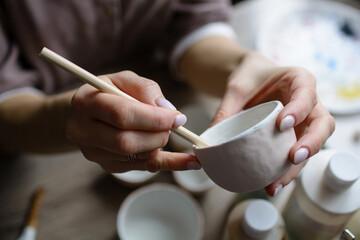Hand-painting homemade ceramic dishes.