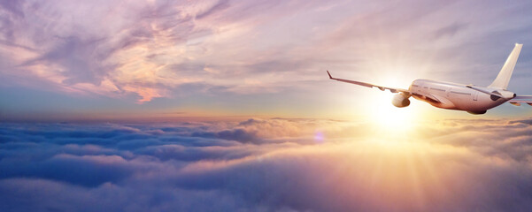 Passenger jetplane flying above clouds in sunset