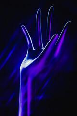 Abstrakcyjna fotografia sztucznej kobiecej ręki w fioletowej poświecie