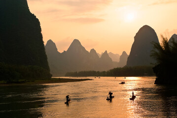 Cormorant fishermen on the Li River (Lijiang) with karst peaks in the background at sunset, near Xingping, Guangxi Province, China