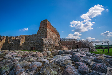 Ruins of Wenecja castle in a field under the sunlight and a blue sky in Poland