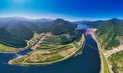 Aerial photography. Bird's eye view of the Sayano-Shushenskaya Hydroelectric Power Station. A powerful dam blocking the mountain river Yenisei, 242 meters high. Mountains and green mountain taiga