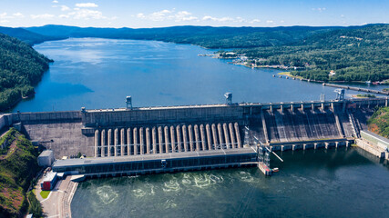 Aerial photography. Bird's eye view of the Krasnoyarsk Hydroelectric Power Plant. A powerful dam blocking the Yenisei River. Depicted on a 10 ruble bill of Russia. Mountains and green mountain taiga