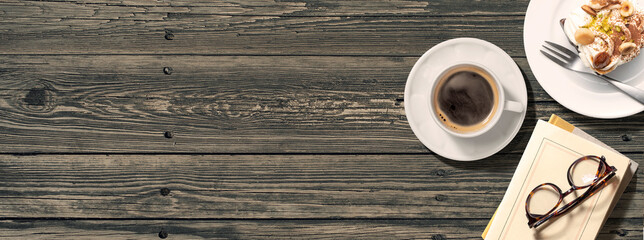 アンティークなテーブルの上にあるコーヒーと本、眼鏡、ケーキ。真上からのアングル