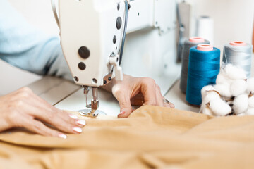 A sewing machine with the hands of a tailor, close-up. Individual designer tailoring.