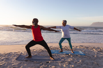 Senior african american couple performing stretching exercise together at the beach