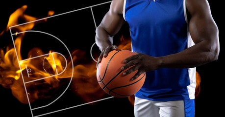 Composition of midsection of basketball player holding basketball over basketball court and fire