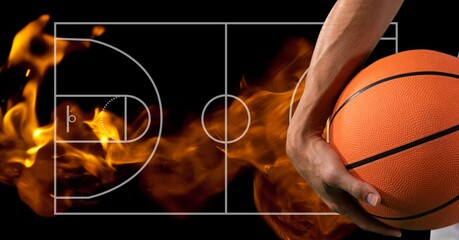 Composition of midsection of basketball player holding basketball over basketball court and flames