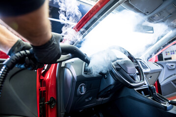 Car service worker cleans interiror with steam cleaner
